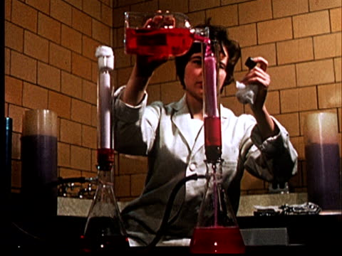 1960 ms woman in lab coat pouring red liquid from glass bottle into tall glass cylinder filtering liquid into a flask/ audio - 1960 stock videos & royalty-free footage
