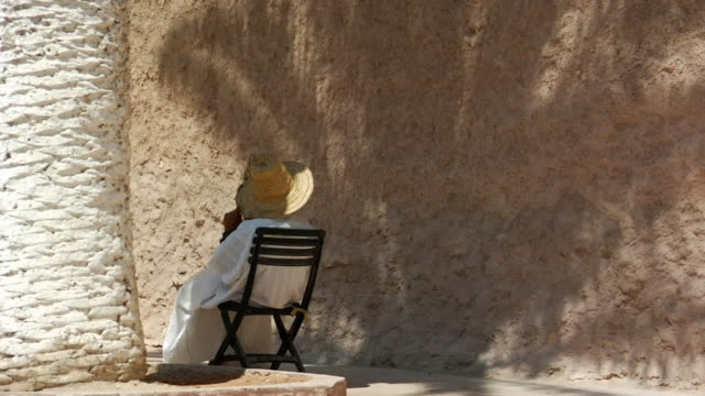 ws woman in large straw hat sitting against wall/ zo ws people walking past/ morocco - straw hat stock videos & royalty-free footage
