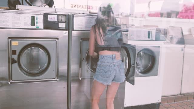 vídeos y material grabado en eventos de stock de woman in laundrette, putting in laundry in machine - lavandería edificio público