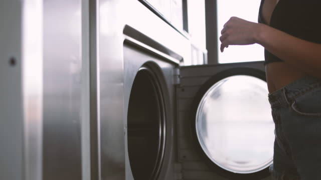 woman in laundrette, putting laundry in machine - washing machine stock videos and b-roll footage