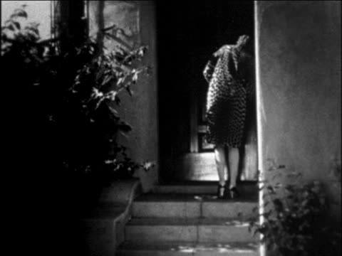 b/w 1929 woman in leopard-skin coat walking down front steps of house / newsreel - coat garment stock videos & royalty-free footage