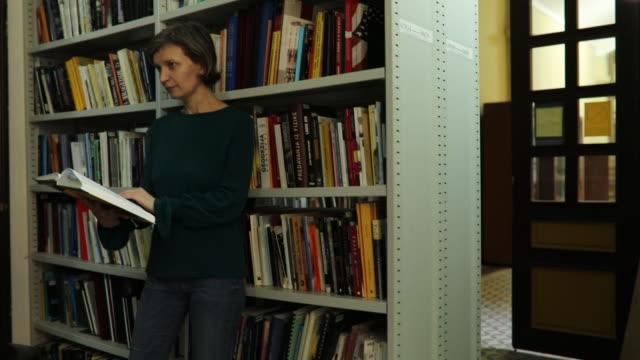frau in der bibliothek ein buch lesen - literatur stock-videos und b-roll-filmmaterial