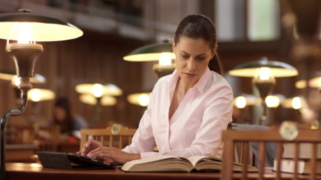 DS Woman in library using a tablet and a book
