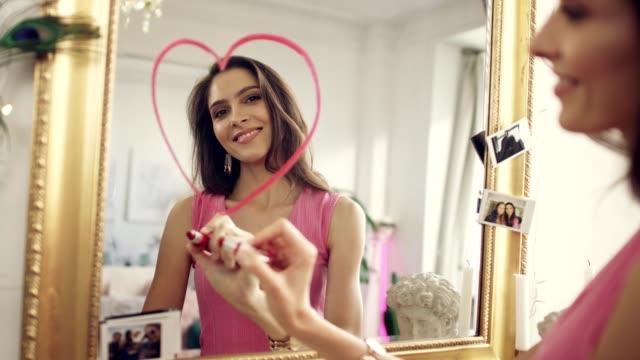 恋に落ちた女鏡に口紅のハートを描く - バレンタインデー点の映像素材/bロール