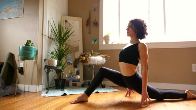 vidéos et rushes de ms woman in low lunge with backbend pose while practicing yoga in bedroom of home - monsieur et madame tout le monde