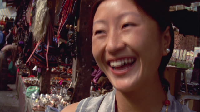 woman in market laughing and smiling at camera available in hd. - bhutan stock videos & royalty-free footage