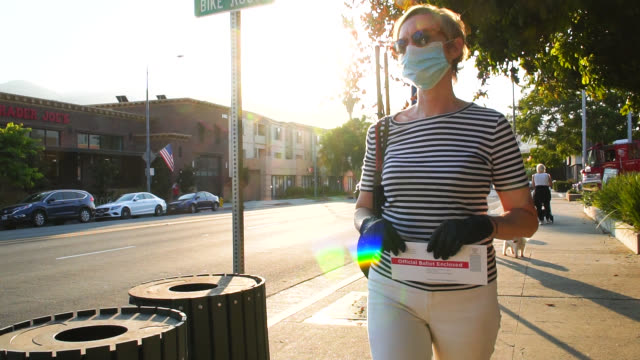 woman in mask and gloves is mailing a vote by mail envelope - answering stock videos & royalty-free footage