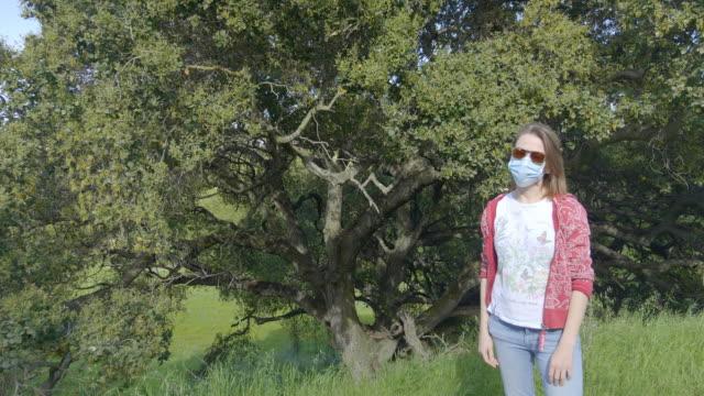stockvideo's en b-roll-footage met vrouw in masker in het park. - vermijden