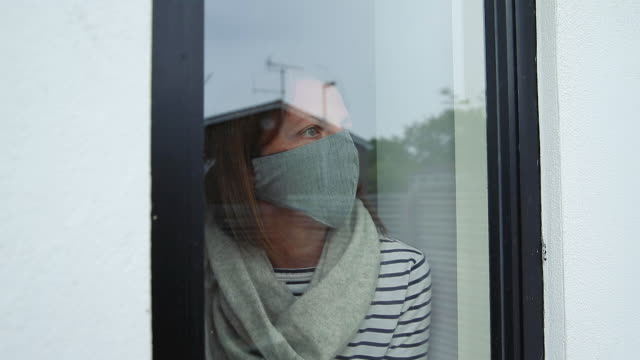 woman in mask looking out of window - lockdown stock-videos und b-roll-filmmaterial