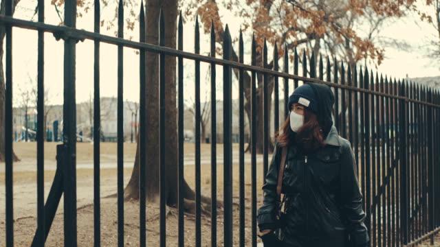 vidéos et rushes de femme au masque de marcher dans le parc - masque de protection