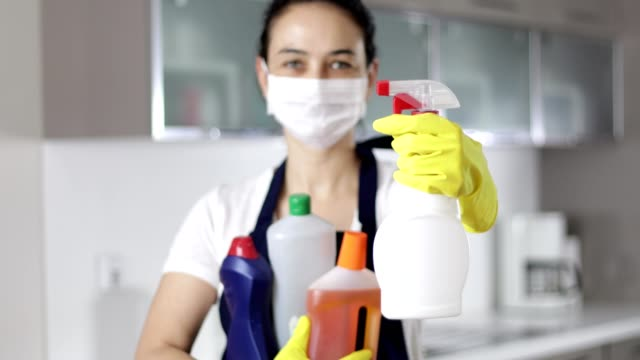woman in mask with cleaning supplies shows spray - spray cleaner stock videos & royalty-free footage