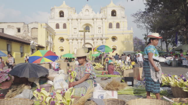 woman in mayan traditional costume makes a palm for palm sunday in front of the church. antigua guatemala. - guatemala stock videos & royalty-free footage