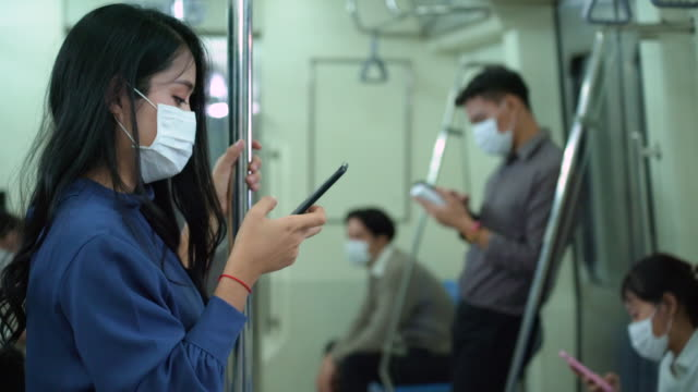 woman in metro train wearing mask to stop spreading covid-19 using mobile phone - public transport stock videos & royalty-free footage