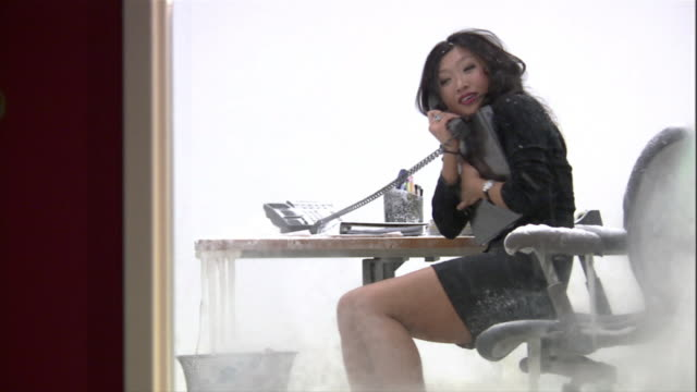 Woman in mini skirt sitting at desk inside frozen office / answering phone