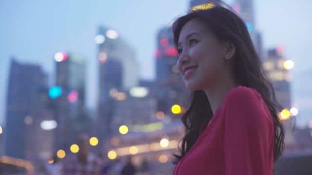 cu woman in modern city with hair blowing - セレクティブフォーカス点の映像素材/bロール