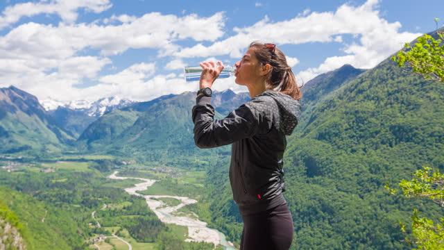 vidéos et rushes de femme dans l'eau potable de montagneside, vallée de montagne à l'arrière-plan - bouteille d'eau minérale
