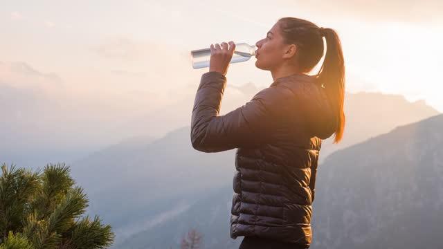 vidéos et rushes de femme dans le flanc de montagne illuminé par la lumière du soleil orange, buvant de la bouteille d'eau - bouteille d'eau minérale