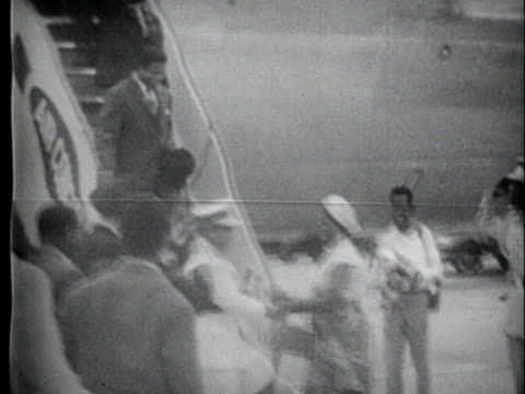 woman in native dress greets a military official with kisses as he disembarks from a sabena airlines plane. - human age stock videos & royalty-free footage
