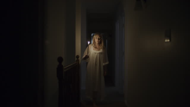 woman in nightgown investigating home with candle during storm at night / springville, utah, united states - springville utah stock videos & royalty-free footage