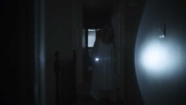 woman in nightgown investigating home with flashlight during storm at night / springville, utah, united states - springville utah stock videos & royalty-free footage