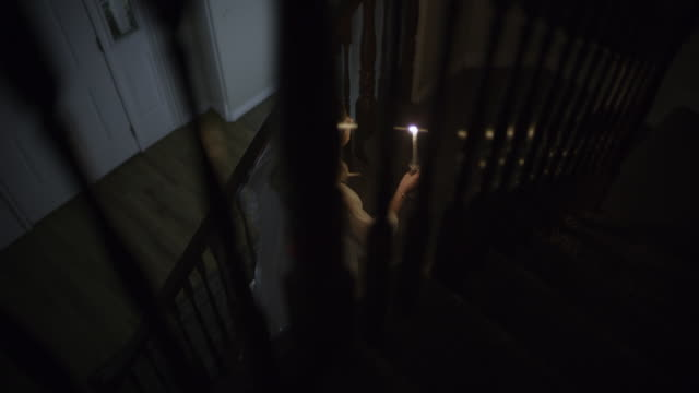 vidéos et rushes de woman in nightgown walking on staircase with candle during storm at night / springville, utah, united states - springville utah
