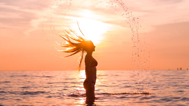 Vrouw in de Oceaan bij zonsondergang