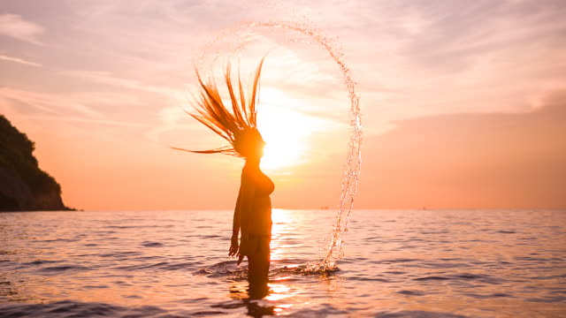 stockvideo's en b-roll-footage met vrouw in oceaan bij zonsondergang - verwonderingsdrang