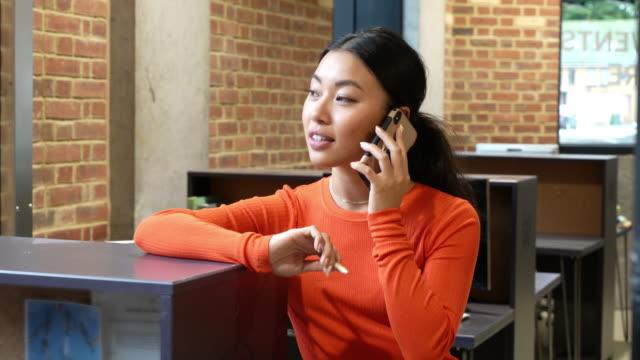stockvideo's en b-roll-footage met woman in office using mobile phone - baksteen