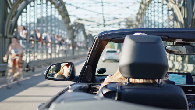 woman in open, black, cabriolet convertible car drives over old city bridge while sunny summer day. - part of a series stock-videos und b-roll-filmmaterial
