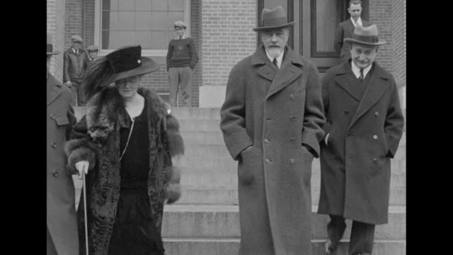 vídeos de stock, filmes e b-roll de woman in ornate hat and fur coat walks down steps with tall man and others the woman is possibly russian grand duchess anastasia nikolaevna romanovna... - alto descrição geral