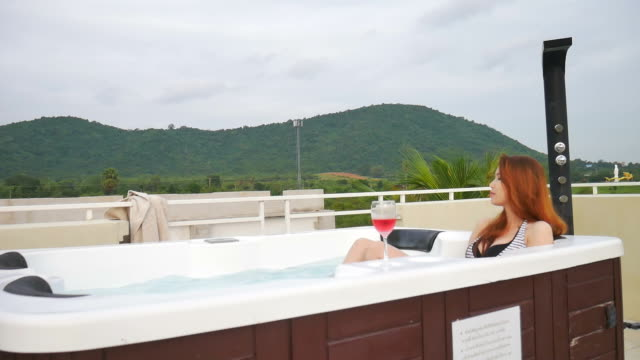 Woman in outdoors jacuzzi with wine at sunset