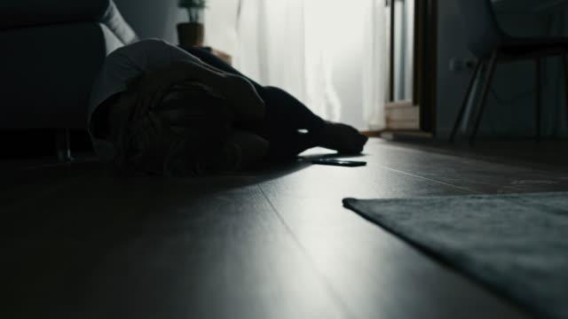 vidéos et rushes de femme de sep dans la douleur couvrant sa tête tout en se trouvant sur le plancher - se tenir la tête entre les mains
