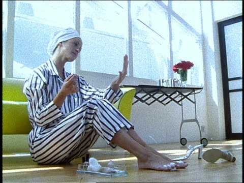 vidéos et rushes de woman in pajamas with towel on head sitting on floor painting fingernails / toenails just painted - manucure