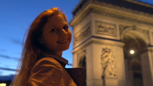 Woman in Paris in front of Arc de Triomphe smiling into camera