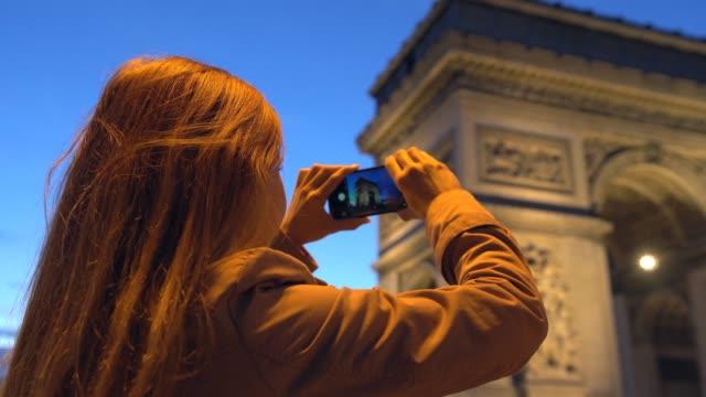vidéos et rushes de femme à paris prendre des photos de l'arc de triomphe de nuit - arc élément architectural