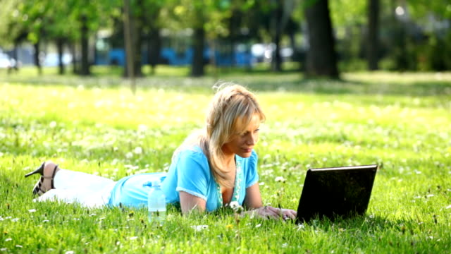 Woman in park using laptop.