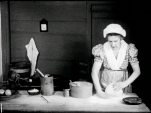 woman in period clothing long dress at kitchen work table kneading dough on floured surface, female hands kneading dough, shaping into round loaf,... - 植民地様式点の映像素材/bロール