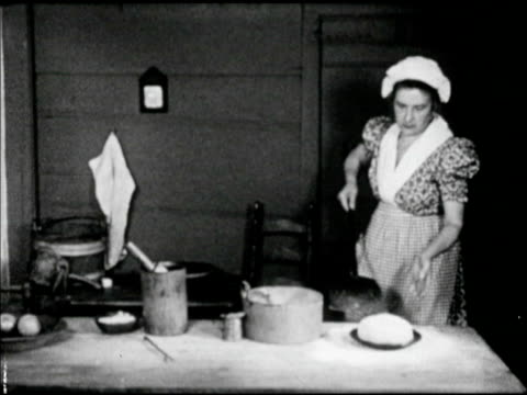 woman in period clothing long dress placing pan of dough onto long handled shovel sliding into hearth brick oven bread - hearth oven stock videos & royalty-free footage
