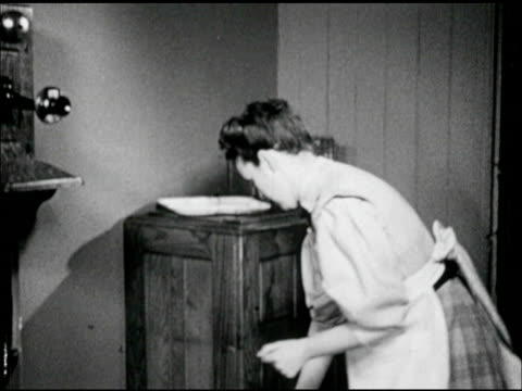 woman in period clothing turning from wall telephone to wooden ice box taking out plate of food carrying out of frame - wood plate stock videos & royalty-free footage