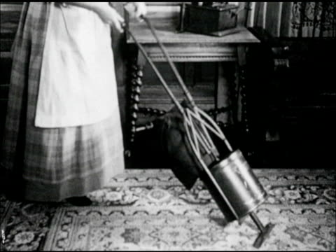 Woman in period clothing using hand squeeze 'vacuum' cleaner on rug woman cranking Gramophone w/ scalloped edge horn Playing music while 'vacuuming'
