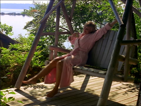 Woman in pink bathrobe drinking coffee + stretching on porch swing / lake in background