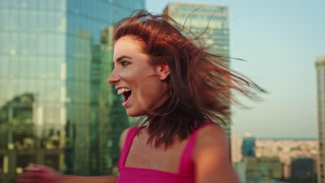 vídeos de stock, filmes e b-roll de mulher de rosa dançando em um telhado. rindo e girando - gesticular