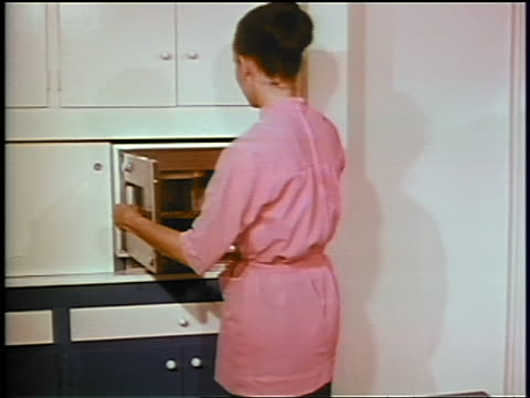 1969 woman in pink dress removing dish from early microwave / industrial - microwave stock videos & royalty-free footage
