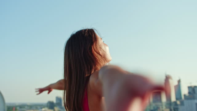kvinna i rosa njuter av utsikt över taket. öppningsarmar - utsträckta armar bildbanksvideor och videomaterial från bakom kulisserna