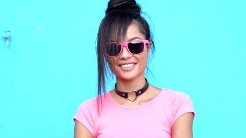vídeos y material grabado en eventos de stock de mujer en pie de traje rosa delante de pared azul - fondo colorido