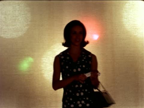 1967 woman in polka dot dress with purse walking towards camera in studio / industrial
