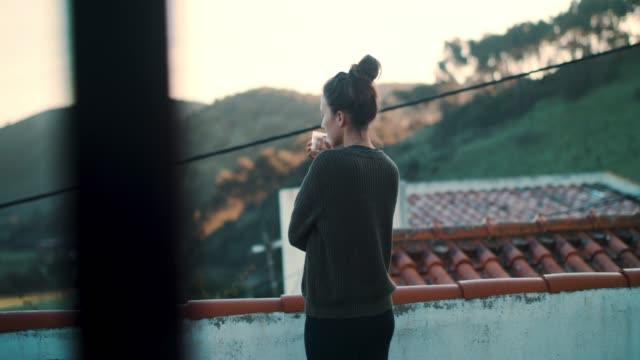 woman in portugal on roof terrace in morning, drinking water - balcone video stock e b–roll