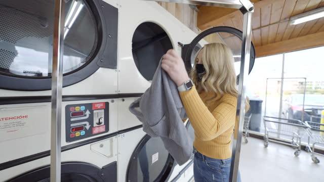 コインランドリーで洗濯をしている保護フェイスマスクの女性 - コインランドリー点の映像素材/bロール