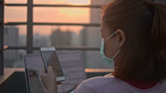 vídeos de stock e filmes b-roll de woman in protective face mask using smartphone on roof terrace,slow motion - texto