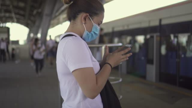 woman in protective face mask using smartphone while waiting for the train on train station platform - gruppo organizzato video stock e b–roll